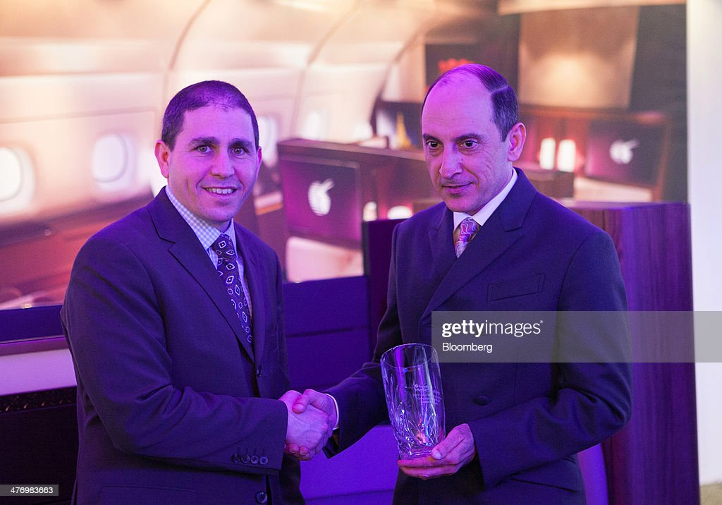 Akbar Al Baker, chief executive officer of Qatar Airways Ltd., right, receives an award from Noah Tratt, vice president of media solutions at Expedia Inc., during the ITB travel fair at Messe Berlin exhibition center in Berlin, Germany, on Thursday, March 6, 2014. Al Baker said yesterday his company will be sticking with hard-wired inflight-entertainment systems. Photographer: Krisztian Bocsi/Bloomberg via Getty Images