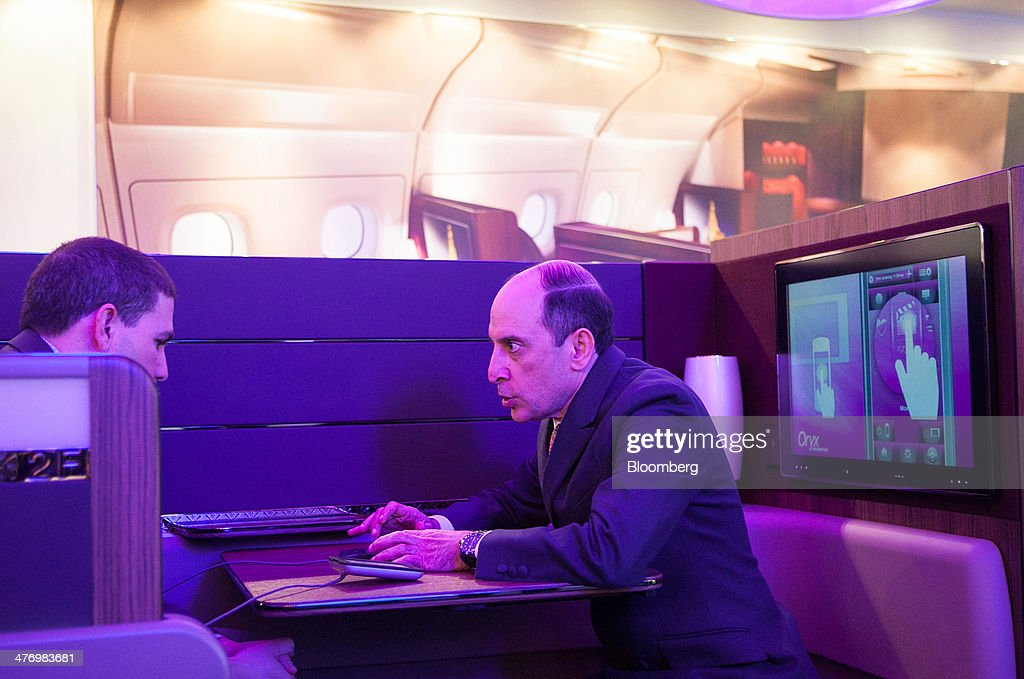 Akbar Al Baker, chief executive officer of Qatar Airways Ltd., right, and Noah Tratt, vice president of media solutions at Expedia Inc., sit in first class seats inside a model Airbus SAS A380 aircraft during the ITB travel fair at Messe Berlin exhibition center in Berlin, Germany, on Thursday, March 6, 2014. Al Baker said yesterday his company will be sticking with hard-wired inflight-entertainment systems. Photographer: Krisztian Bocsi/Bloomberg via Getty Images