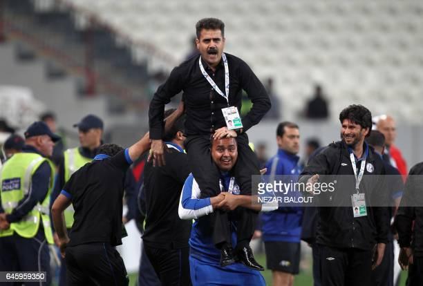 Akbar Pourmousavi head coach of Iran's Esteghlal Khuzestan club is carried by players after they won an Asian Champions League Group B football match...