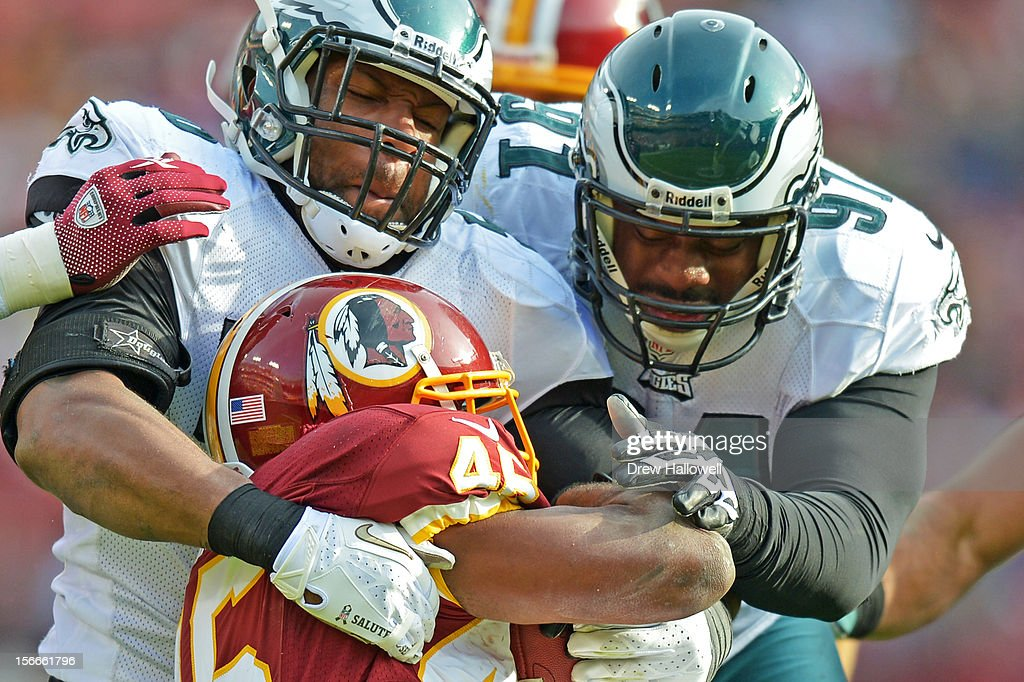 Akeem Jordan #56 and Fletcher Cox #91 of the Philadelphia Eagles tackles Alfred Morris #46 of the Washington Redskins at FedEx Field on November 18, 2012 in Landover, Maryland. The Redskins won 31-6.