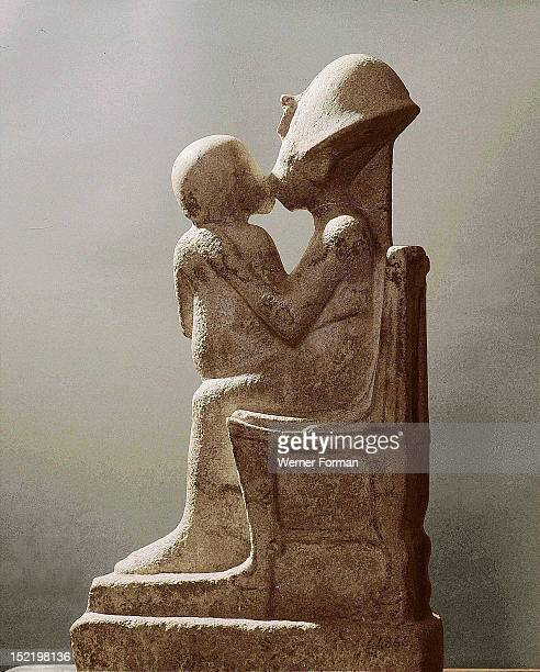 Akhenaten kisses his daughter as she sits on his lap An unfinished statue Full profile view Egypt Ancient Egyptian Amarna period c 1373 1357 BC Tell...