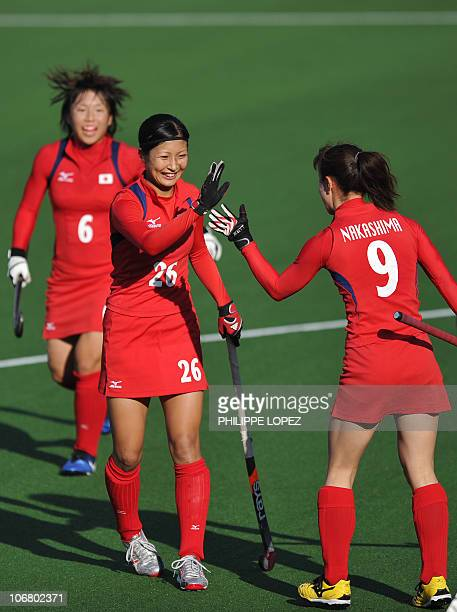 Aki Mitsuhashi of Japan celebrates with her teammate Mie Nakashima after she scored a goal against Kazakhstan during their field hockey match of the...