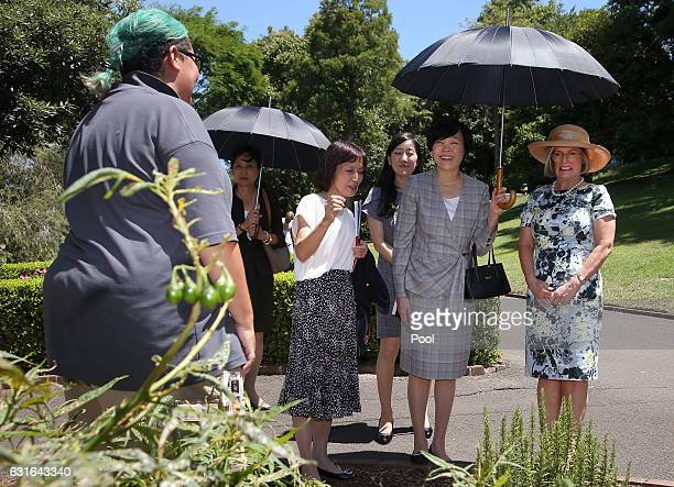 Akie Abe second right wife of Japanese Prime Minister Shinzo Abe holds an umbrella for herself and Lucy Turnbull right wife of Australian Prime...
