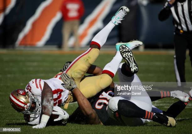 Akiem Hicks of the Chicago Bears tackles Carlos Hyde of the San Francisco 49ers in the first quarter at Soldier Field on December 3 2017 in Chicago...