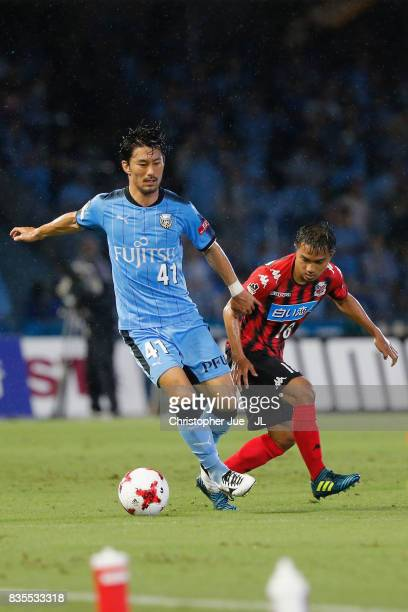 Akihiro Ienaga of Kawasaki Frontale controls the ball under pressure of Chanathip Songkrasin of Consadole Sappporo during the JLeague J1 match...