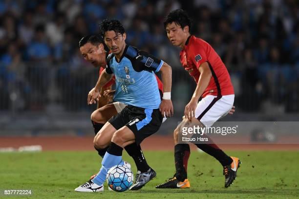 Akihiro Ienaga of Kawasaki Frontale controls the ball under pressure of Tomoaki Makino and Wataru Endo of Urawa Red Diamonds during the AFC Champions...