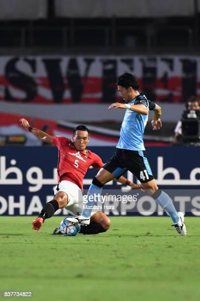 Akihiro Ienaga of Kawasaki Frontale is tackled by Tomoaki Makino of Urawa Red Diamonds during the AFC Champions League quarter final first leg match...