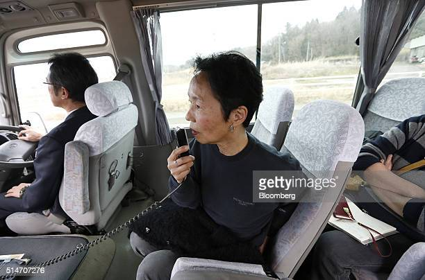 Akiko Onuki speaks into a microphone as she guides a tour traveling through evacuation zone areas damaged by the 2011 earthquake and tsunami onboard...