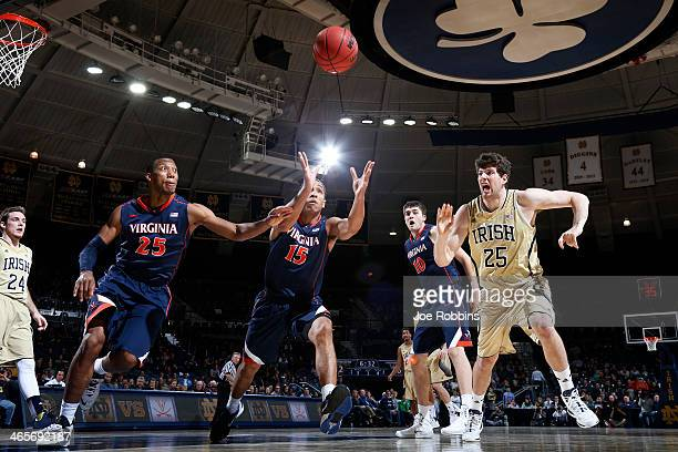 Akil Mitchell and Malcolm Brogdon of the Virginia Cavaliers go for a loose ball against Tom Knight of the Notre Dame Fighting Irish during the first...
