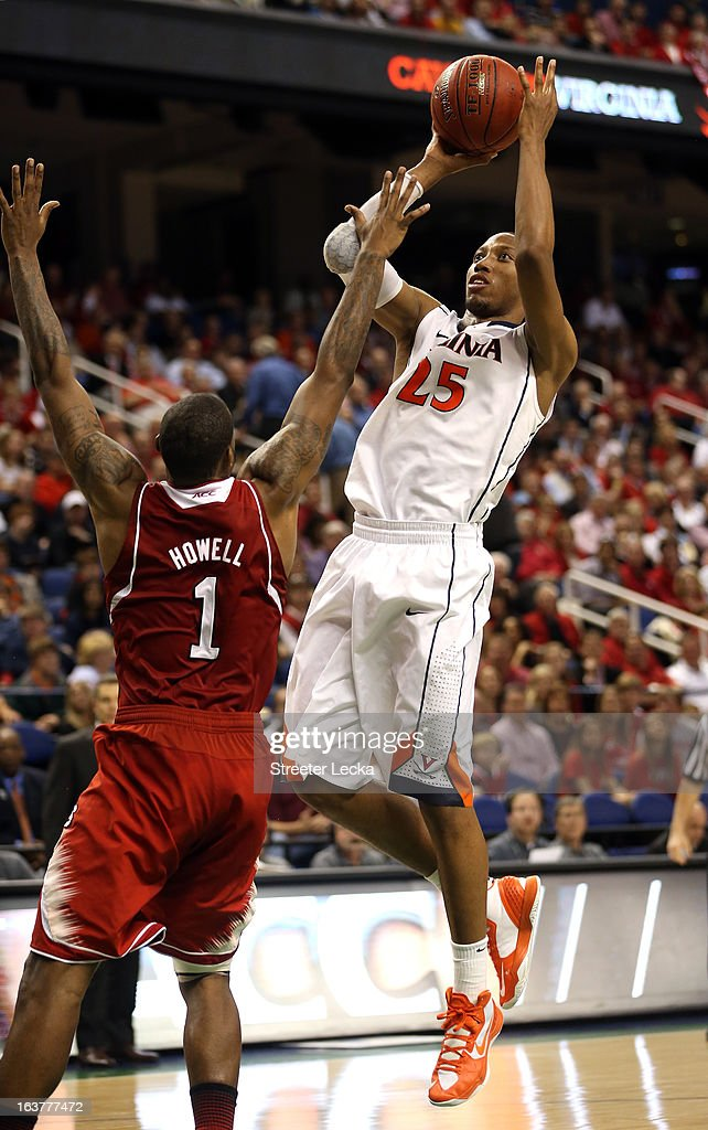 Akil Mitchell of the Virginia Cavaliers shoots over Richard Howell of the North Carolina State Wolfpack during the quarterfinals of the Men's ACC...