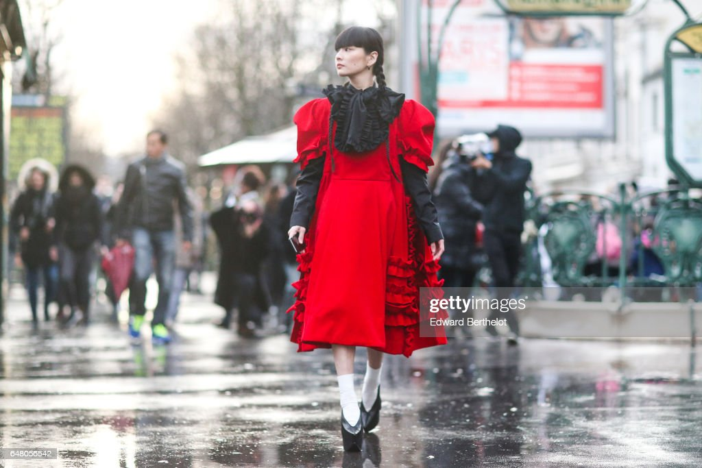 Akimoto Kozue is wearing a black and red dress with ruffles, white socks, and black shoes, outside the Comme des Garcons show, during Paris Fashion Week Womenswear Fall/Winter 2017/2018, on March 4, 2017 in Paris, France.