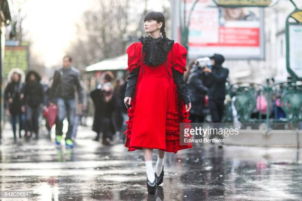 Akimoto Kozue is wearing a black and red dress with ruffles white socks and black shoes outside the Comme des Garcons show during Paris Fashion Week...