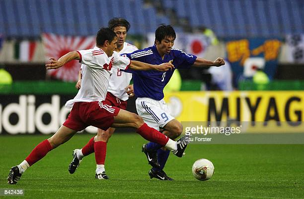 Akinori Nishizawa of Japan tries to go past Fatih Akyel of Turkey during the FIFA World Cup Finals 2002 Second Round match played at the Miyagi...