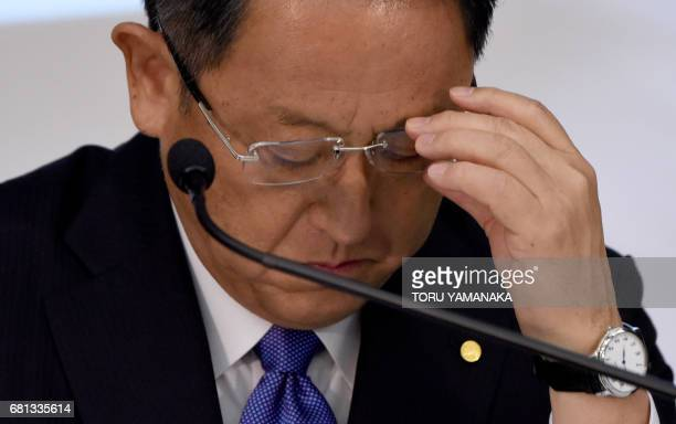Akio Toyoda president of Japan's auto giant Toyota Motor adjusts his glasses as he listens to questions during a press conference to announce the...