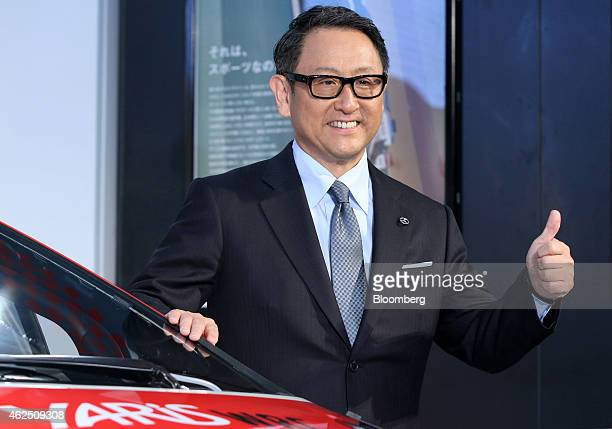 Akio Toyoda president of Toyota Motor Corp poses for a photograph standing next to a Yaris WRC test car during a news conference in Tokyo Japan on...