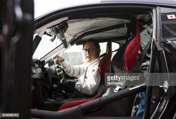 Akio Toyoda president of Toyota Motor Corp reacts as he sits in the driver's seat of the Toyota 86 Morizo coupe after the unveiling of 'GR' sports...