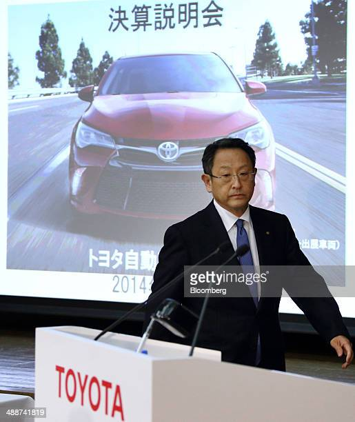 Akio Toyoda president of Toyota Motor Corp walks past a screen displaying an image of the company's Camry sedan as he arrives for a news conference...