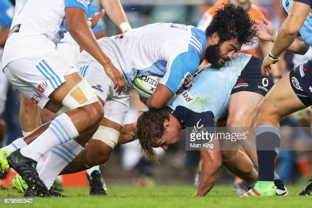 Akira Ioane of the Blues is tackled by Michael Hooper of the Waratahs during the round 11 Super Rugby match between the Waratahs and the Blues at...