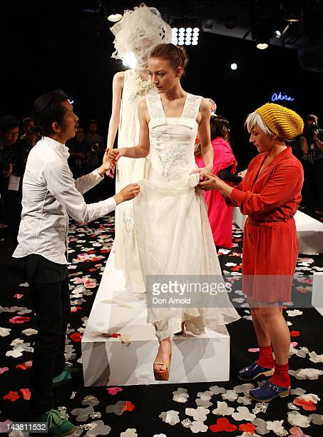 Akira Isogawa helps a model into position on day five of Mercedes Benz Fashion Week Australia Spring/Summer 2012/13 at the Overseas Passenger...