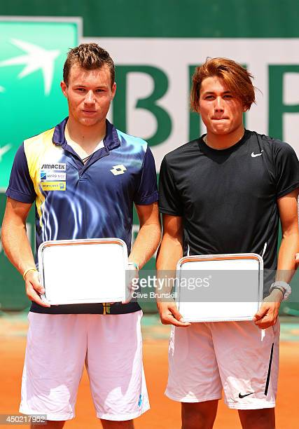 Akira Santillan of Australia and Lucas Miedler of Austria poses with their trophies following their defeat in the boys' doubles final match against...