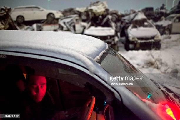 Akira Sugawara a security guard escapes the cold at work in a yard where cars salvaged from last year's tsunami are piled waiting for owners to come...