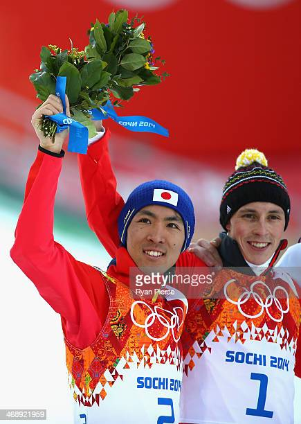Akito Watabe of Japan and Eric Frenzel of Germany celebrate during the flower ceremony after the Nordic Combined Individual NH / 10 km during day...