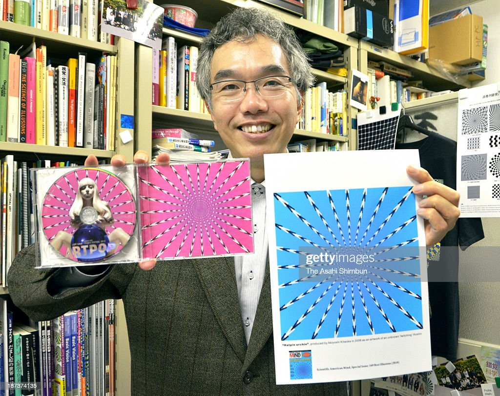 Akiyoshi Kitaoka, a professor of perceptual psychology at Ritsumeikan University, holds the images he designed, which were adopted in Lady Gaga's CD package art on November 7, 2013 in Kyoto, Japan. In the pictures, objects resembling the spikes of a sea urchin and laid out in a radial fashion give viewers the impression that they are moving due to a trick of the eye.