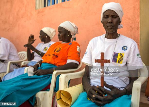 Akol Adut holds a wooden cross during a prayer session at Tomping Presbyterian Church after taking part in a silent march with women from more than...