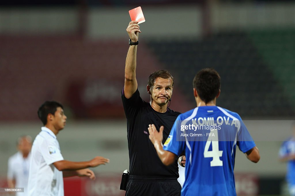 Akramjon Komilov of Uzbekistan is sent off by referee Pavel Kralovec during the FIFA U-17 World Cup UAE 2013 Round of 16 match between Honduras and Uzbekistan at Sharjah Stadium on October 28, 2013 in Sharjah, United Arab Emirates.