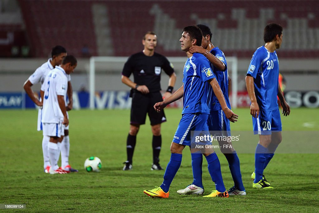 Akramjon Komilov of Uzbekistan leaves the pitch after being sent off by referee Pavel Kralovec during the FIFA U-17 World Cup UAE 2013 Round of 16 match between Honduras and Uzbekistan at Sharjah Stadium on October 28, 2013 in Sharjah, United Arab Emirates.