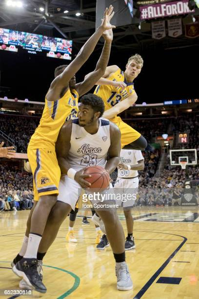 Akron Zips C Isaiah Johnson is defended by Kent State Golden Flashes F Jimmy Hall and Kent State Golden Flashes G Mitch Peterson during the first...