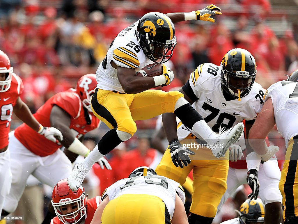Akrum Wadley #25 of the Iowa Hawkeyes leaps over teammate Ike Boettger #75 as he carries the ball in the first half agianst the Rutgers Scarlet Knights at High Point Solutions Stadium on September 24, 2016 in Piscataway, New Jersey.
