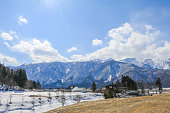 akuba mountain range  and  Hakuba village houses  in the winter with snow on the mountain and blue sky and clouds background in Hakuba  Nagano Japan.
