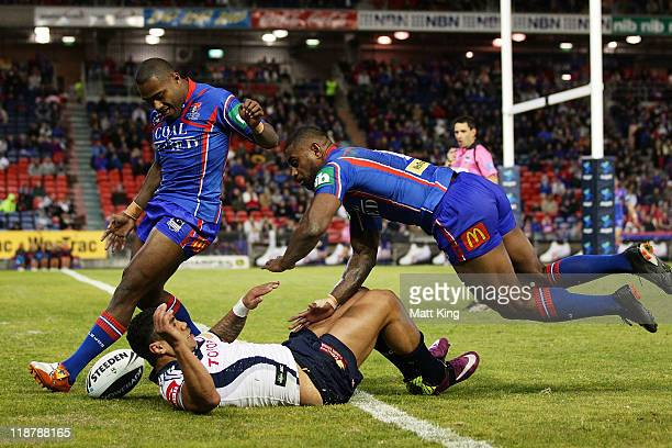 Akuila Uate and Wes Naiqama of the Knights and Willie Tonga of the Cowboys scramble for the ball in the Knights tryline during the round 18 NRL match...