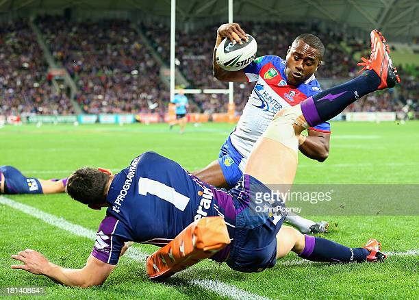 Akuila Uate of the Knights fends off a tackle from Billy Slater of the Storm to score a try during the NRL Second Semi Final match between the...