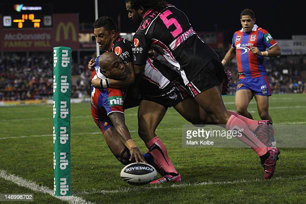Akuila Uate of the Knights is tackled by Benji Marshall and Lote Tuqiri of the Tigers as he scores a try during the round 16 NRL match between the...