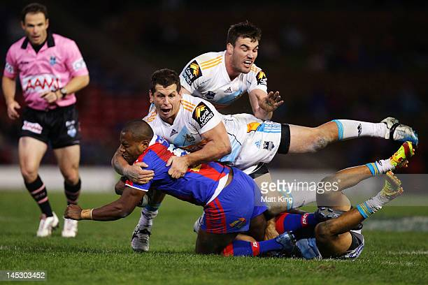Akuila Uate of the Knights is tackled heavily by Greg Bird and Luke Douglas of the Titans during the round 12 NRL match between the Newcastle Knights...