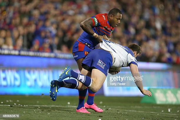Akuila Uate of the Knights picks up Josh Morris of the Bulldogs during the round 25 NRL match between the Newcastle Knights and the Canterbury...