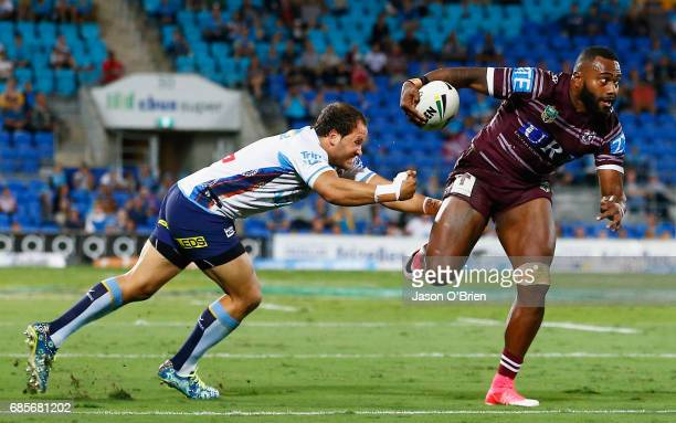 Akuila Uate of the Sea Eagles breaks the tackle of Tyrone Roberts of the Titans during the round 11 NRL match between the Gold Coast Titans and the...