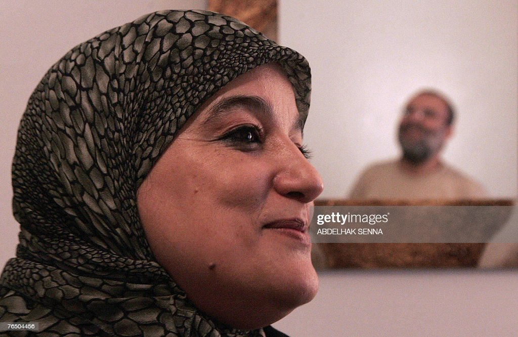 ... (L) poses 04 September 2007 as her husband <b>Abdellah Chibani</b> is reflected ... - al-adl-wal-ihssane-islamist-association-figurehead-nadia-yassine-04-picture-id76504456