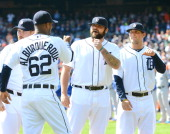 Al Alburquerque of the Detroit Tigers is greeted by teammates Joba Chamberlain and Ian Krol during player introductions prior to the game against the...