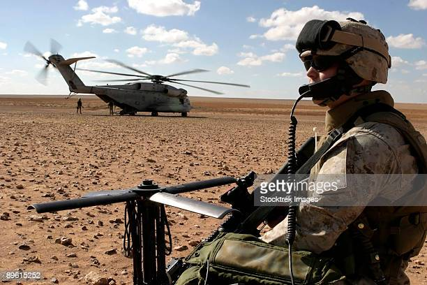 Al Asad, Iraq, November 18, 2004 - A marine assembles a radio antenna as a CH-53E Super Stallion helicopter lands near Iraqi Border Fort Number 12.