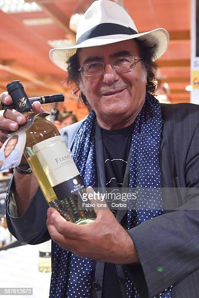 Al Bano Blake signs autographs on his bottles of wine as he attends a meet and greet with the public on August 8 2016 in Marina di Gioisa Jonica Italy