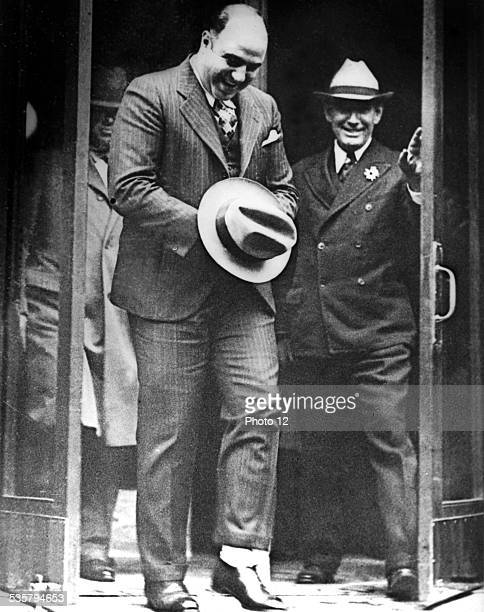 Al Capone hiding handcuffs under his hat is leaving the Atlanta Court after the hearing of his request for release November 1932 United States...