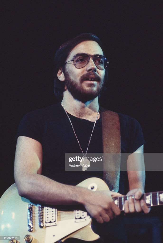 Al Di Meola US jazz guitarist holding his guitar where the fretboard meets the body during a live concert performance with his band Return to Forever...