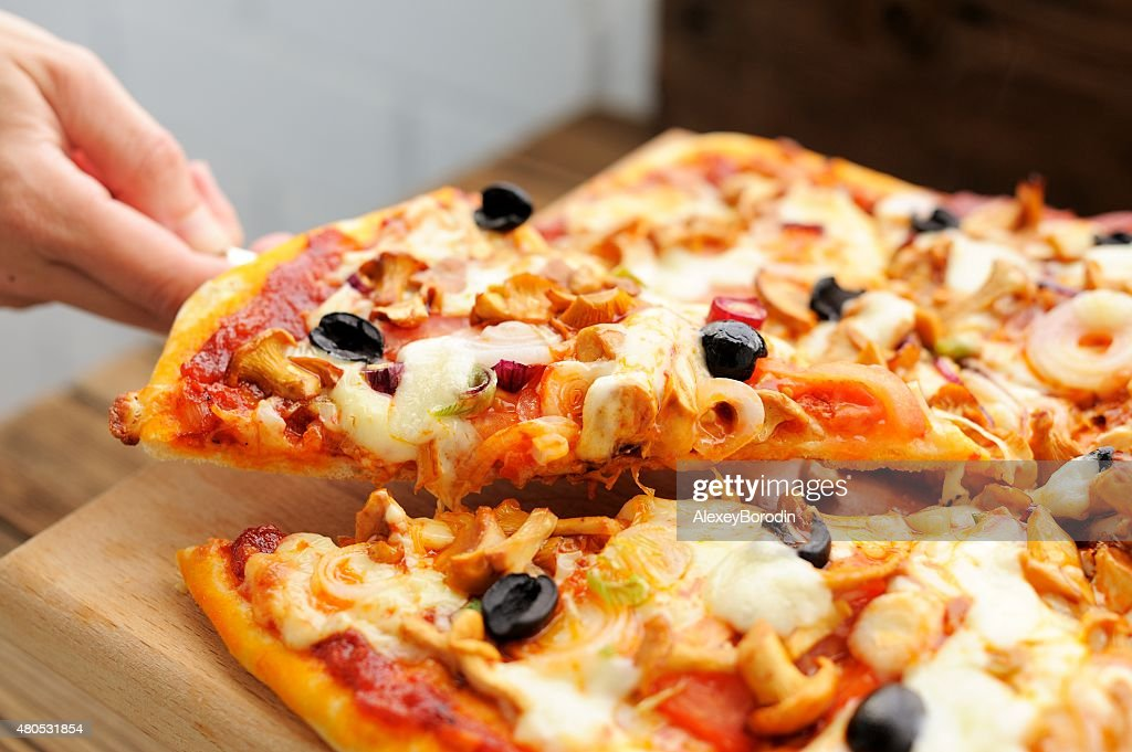 Al funghi pizza cut in sectors with one piece taken : Stock Photo