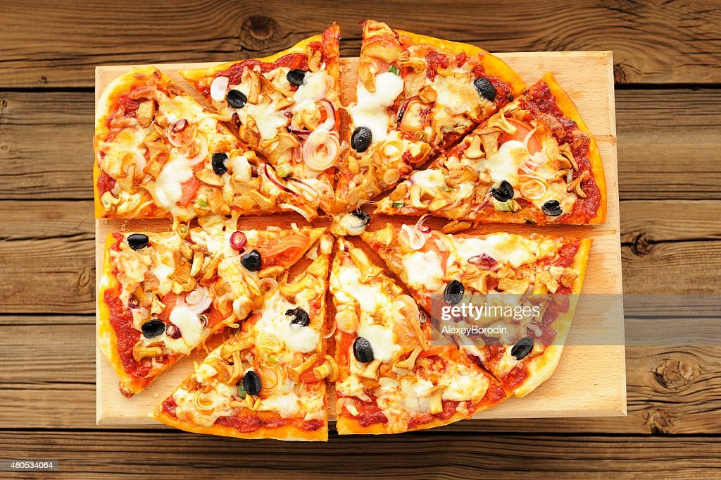 Al funghi pizza with olives cut in sectors on wooden : Bildbanksbilder