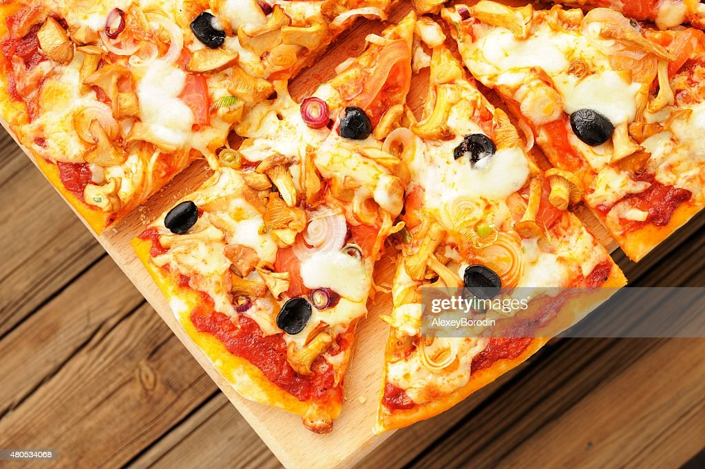 Al funghi pizza with olives cut in sectors on wooden : Stockfoto