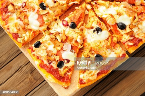 Al funghi pizza with olives cut in sectors on wooden : Stock Photo