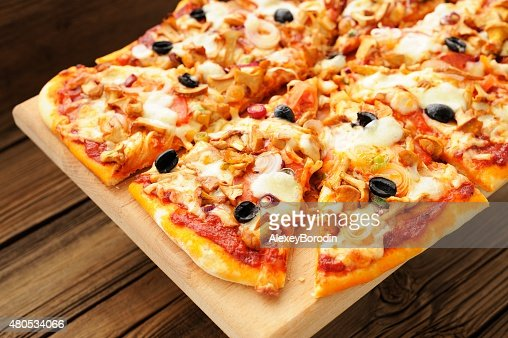 Al funghi pizza with olives cut in sectors : Stock Photo